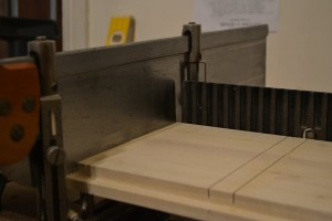 Place the board on top of the shims and saw the shoulders of the dado until the saw bottoms out on the depth stops.