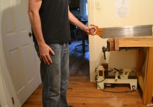 Showing poor form while using a 28 miter box saw with low hang. The elbow is too high, cocking the wrist upwards.