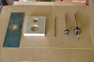 """Tools for boring, from left to right:  wear plate, aluminum spacer, 3/16"""" brad point bit, 1/4"""" piloted counterbore with depth stop, 7/16"""" piloted counterbore with depth stop."""