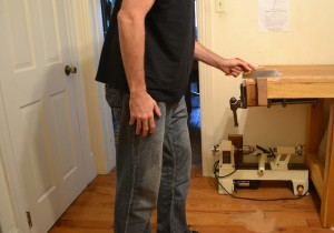 Showing better form while using a small patternmaker's saw with high hang.  The elbow has been raised by standing more upright, bringing the forearm into alignment with the wrist.  In practice, I would prefer to lean and crouch as shown in Figure 5, but angle the saw and/or lower the work.  I find that this engages more of the lower body, increasing power, accuracy, and comfort.